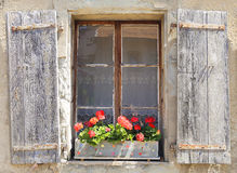 Beautiful window with flower box. Beautiful old window with red flowers Royalty Free Stock Image