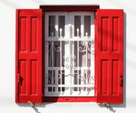 Beautiful window with grille and red shutters Stock Images