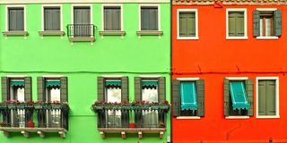 Beautiful windows with green shutters and balcony with flowers on red and green wall. Colorful houses on Burano island near Venice stock photography