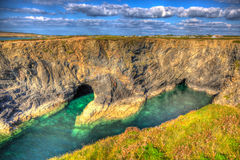 Beautiful Wine Cove Cornwall coast turquoise blue sea with snorkellers in HDR Stock Image