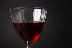 A beautiful wine glass full of a semisweet red liquid. A glass of wine on a black background. Delicious sweet wine. Copy Royalty Free Stock Photography