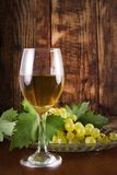 Wine glass with table white wine and green grape on plate with vine stock photos