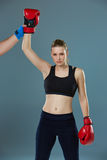 Beautiful winner. Blond hair woman in red boxing. Beautiful winner. Beautiful blond hair woman in red boxing gloves standing on gray background. Concept of Stock Photography