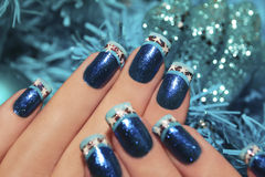 Beautiful winter blue manicure. Beautiful winter blue manicure with snowflakes on a brilliant background in the form of snowflakes stock photography