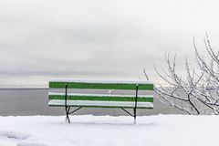 Beautiful winter day at Odderoya in Kristiansand, Norway. Green bench covered in snow. The ocean is seen in the. Beautiful winter day at Odderoya in Kristiansand Stock Photo