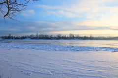 Beautiful winter day. Snow on the bank of the river. Trees under the snow. The low winter sun royalty free stock image