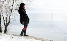 Beautiful winter girl on frozen river bank Royalty Free Stock Images
