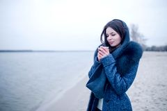 Beautiful winter girl on the river bank with a glass of coffee stock image
