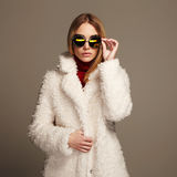 Beautiful winter girl in white fur and sunglasses. winter fashion.young woman. Beautiful winter girl in white fur and sunglasses. winter fashion beauty young stock image