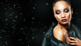 Beautiful winter glamour woman. Upscale Indian woman wearing green fur coat and dramatic red lipstick on black background Royalty Free Stock Photo