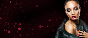 Beautiful winter glamour woman. Upscale Indian woman wearing green fur coat and dramatic red lipstick on black background Royalty Free Stock Image