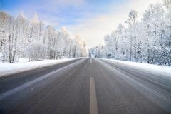 Winter landscape with asphalt road,forest and blue sky. Royalty Free Stock Images