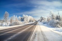 Winter landscape with asphalt road,forest and blue sky. Royalty Free Stock Photography