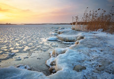 Beautiful winter landscape with frozen lake and sunset sky. Comp Stock Photography