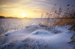 Beautiful winter landscape with frozen lake and sunset sky. Stock Image