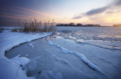Beautiful winter landscape with frozen lake and sunset sky. Royalty Free Stock Photography