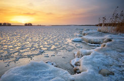 Beautiful winter landscape with frozen lake and sunset sky. Stock Images