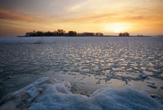 Beautiful winter landscape with frozen lake and sunset sky. Royalty Free Stock Images