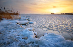 Beautiful winter landscape with frozen lake and sunset sky. Stock Photos
