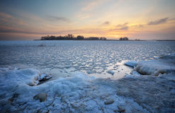 Beautiful winter landscape with frozen lake and sunset sky. Stock Photo