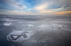Beautiful winter landscape with frozen lake and sunset Stock Photography