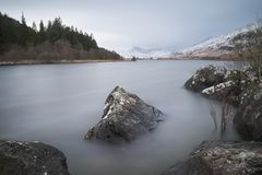 Beautiful Winter landscape image of Llynnau Mymbyr in Snowdonia. Beautiful sunrise landscape image in Winter of Llynnau Mymbyr in Snowdonia National Park with Royalty Free Stock Image