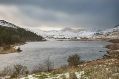 Beautiful Winter landscape image of Llynnau Mymbyr in Snowdonia. Beautiful sunrise landscape image in Winter of Llynnau Mymbyr in Snowdonia National Park with Royalty Free Stock Photos