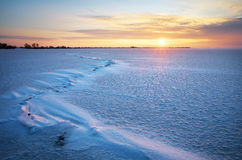 Beautiful winter landscape with lake, crack and sunset sky. Stock Images