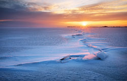 Beautiful winter landscape with lake, crack and sunset sky. Stock Image