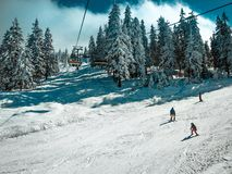 People having a good time on the slopes on a sunny day. Royalty Free Stock Image