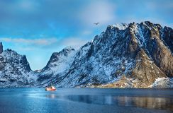 Beautiful winter landscape of picturesque mountains with fishing boat in Lofoten islands. In Norwegian Sea, Norway Royalty Free Stock Photos