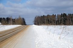 Purified empty suburban sand-strewn road through a snowfield and a forest under blue sky with white clouds on frosty bright sunny Stock Photos