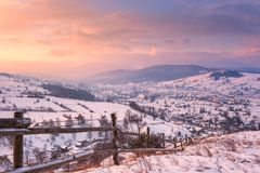 Beautiful winter landscape in soft sunset light, alpine valley surrounded by wooded mountains. Carpathians stock images