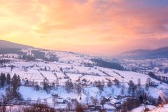 Beautiful winter landscape in soft sunset light, alpine valley surrounded by wooded mountains. Carpathians royalty free stock images