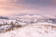 Beautiful winter landscape in soft sunset light, alpine valley surrounded by wooded mountains. Carpathians stock photo