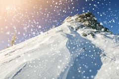 Beautiful winter landscape. Steep mountain hill slope with white. Deep snow, distant mountain range panorama, large snowflakes and bright shining sun rays on royalty free stock images