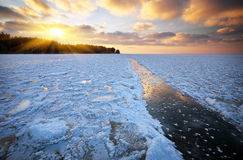 Beautiful winter landscape with sunset and frozen lake Stock Images