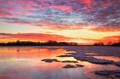 Beautiful winter landscape with sunset sky and frozen lake Royalty Free Stock Photo