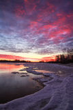 Beautiful winter landscape with sunset sky and frozen lake Royalty Free Stock Image