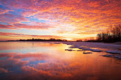 Beautiful winter landscape with sunset sky and frozen lake Stock Photography