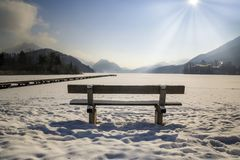 Beautiful winter landscape with a wooden bench standing near the lake stock photography