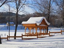 Beautiful winter landscape with a wooden pergola covered with a thick layer of snow on a Sunny frosty day stock photography