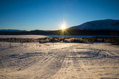 Beautiful winter picture with snowmobile trails. Beautiful scenery picture with snowmobile trails that lead down to the lake, mountains and sun in the background Royalty Free Stock Photography