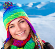 Beautiful winter portrait of woman. Wearing cute colorful hat and scarf standing on snowy mountains background, wintertime holidays Royalty Free Stock Photo