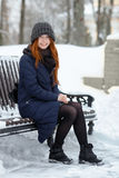 Beautiful winter portrait of young adorable redhead woman in cute knitted hat winter having fun sitting on bench snowy park Stock Photos