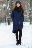 Beautiful winter portrait of young adorable redhead woman in cute knitted hat winter having fun on snowy park path Royalty Free Stock Images