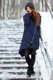 Beautiful winter portrait of young adorable redhead woman in cute knitted hat winter having fun on snowy park stairway Stock Images