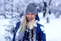 Beautiful winter portrait of young woman in the winter snowy scenery. Beautiful girl in winter clothes. Royalty Free Stock Image
