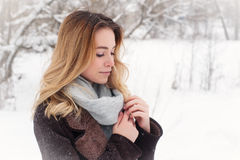 Beautiful winter portrait of young woman in the winter snowy scenery Stock Photography