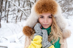 Beautiful winter portrait of young woman in the winter snowy scenery.  Royalty Free Stock Image